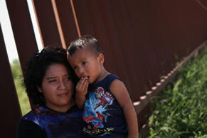 A woman from Guatemala holds her 2-year old son along the border wall last month...
