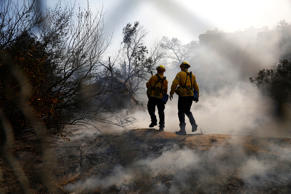 A vehicle drives through smoke from a wildfire near Pulga, Calif., Sunday, Nov. ...