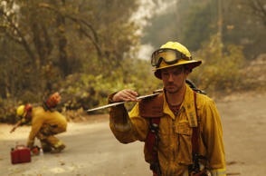 Shawn Slack carries a chainsaw after felling trees burned in the Camp Fire, Mond...