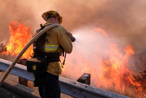 A firefighter battles a fire along the Ronald Reagan (118) Freeway in Simi Valle...
