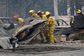 Cal Fire firefighters comb through a house destroyed by the Camp Fire in Paradis...