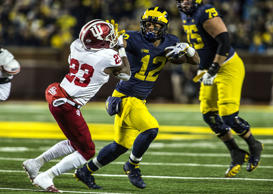 Michigan's Chris Evans (12) holds his arm out to keep away Indiana's Jaylin Will...
