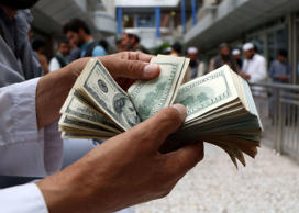 A money changer counts U.S. dollar banknotes at money change market in Herat pro...