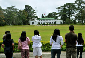 Tourists gaze at the Mansion House, the summer residence of the Philippine presi...