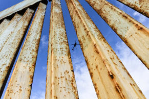 A helicopter monitors the U.S. border fence from above, seen from Tijuana, Mexic...