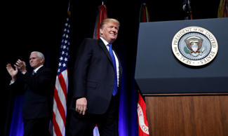 U.S. President Donald Trump walks to the podium after being introduced by Vice P...