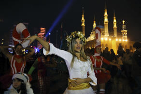 A Lebanese woman dances in front of Muhammad al-Amin Mosque during Christmas cel...