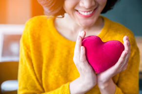 close up of  woman  hands in yellow sweater holding pink heart. people, age, fam...