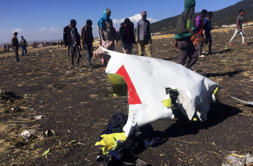 People walk past a part of the wreckage at the scene of the Ethiopian Airlines F...