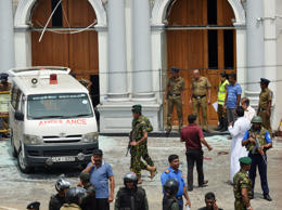 An ambulance is seen outside the church premises with gathered people and securi...