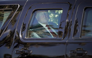 President Donald Trump is seen sitting inside his armored SUV as he departs his ...