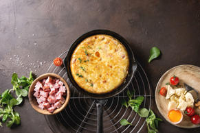 Spanish potato omelette tortilla with bacon served in cast-iron pan on cooling r...