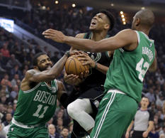Boston Celtics' Kyrie Irving (11) forces a jump ball against Milwaukee Bucks' Gi...