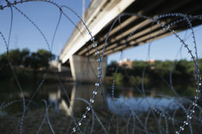 A truck drives near the US-Mexico border reinforced with barb wire and reading '...