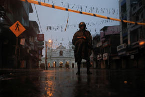 A soldier stands guard at St. Anthony's Shrine during heavy rain, days after a s...
