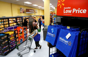 Customers push carts past reusable Walmart shopping bags during the grand openin...