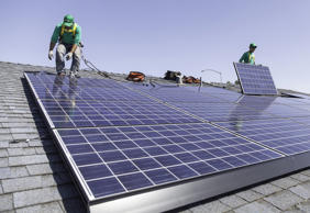 SolarCity workers install solar panels on the roof of a home.