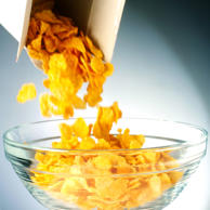 Cornflakes tumbling out of box and into bowl