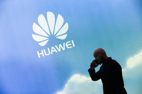 An attendee speaks on his mobile phone at the Huawei Technologies Co Ltd. stand ...