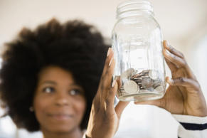 Woman holding jar of change.