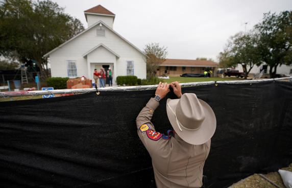 A Texas state trooper helps erect a fence around the site of the shooting at the...