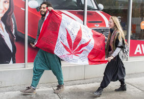 People hold up a Canadian flag with a marijuana logo on it outside a government ...