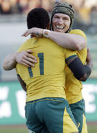 Australia's Marika Koroibete, left, is cheered by teammate David Pocock after sc...