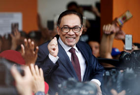 Malaysian politician Anwar Ibrahim gestures as he leaves a hospital where he is ...