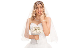 Nervous young bride biting her nails and looking at the camera isolated on white...